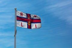Vuelo nacional real de la bandera de la institución RNLI del bote salvavidas sobre la estación del salvavidas en Southwould, Rein foto de archivo libre de regalías