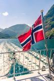 Vuelo noruego de la bandera en la cubierta en popa del barco de cruceros del fiordo foto de archivo