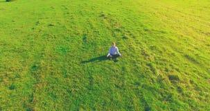 Vuelo orbital bajo alrededor del hombre en hierba verde con el coj?n del cuaderno en el campo rural amarillo almacen de metraje de vídeo