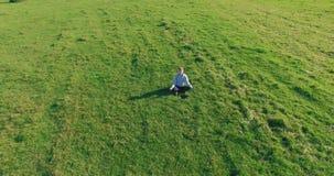 Vuelo orbital bajo alrededor del hombre en hierba verde con el coj?n del cuaderno en el campo rural amarillo almacen de video