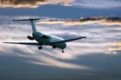 Vuelo plano del avi?n de pasajeros en el cielo de la tarde en la puesta del sol imágenes de archivo libres de regalías