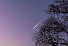 Vuelo plano a través de un cielo púrpura Imágenes de archivo libres de regalías