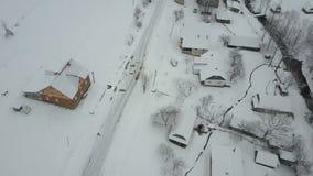 Vuelo rápido sobre un coche que mueve encendido el camino del invierno en pueblo cárpato Opinión del ojo de pájaro de casas nevad metrajes
