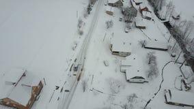Vuelo rápido sobre un coche que mueve encendido el camino del invierno en pueblo cárpato Opinión del ojo de pájaro de casas nevad almacen de metraje de vídeo