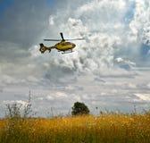 Vuelo sobre campo-tomar del helicóptero sobre un prado floreciente contra un cielo nublado Imagen de archivo