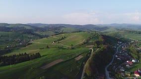 Vuelo sobre el bosque en las montañas y el pueblo Opinión aérea el ucraniano Cárpatos almacen de metraje de vídeo