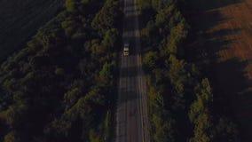 Vuelo sobre el camino con tráfico en la antena caliente de la puesta del sol del verano almacen de video