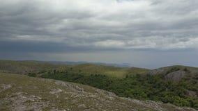 Vuelo sobre el camino de tierra rural de la montaña hacia un borde del acantilado Vista aérea que sorprende de rocas, de bosques  metrajes