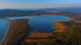 Vuelo sobre el lago hermoso Blagodatnoe, rodeado por verano y bosque y montañas del otoño en el fondo metrajes