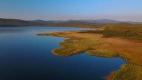 Vuelo sobre el lago hermoso Blagodatnoe, rodeado por verano y bosque y montañas del otoño en el fondo almacen de metraje de vídeo