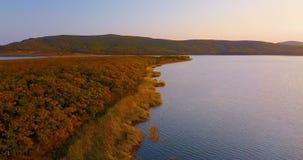 Vuelo sobre el lago hermoso Blagodatnoye rodeado con los bosques y las montañas verdes en el fondo metrajes