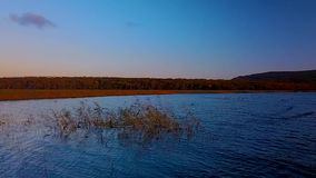 Vuelo sobre el lago hermoso Blagodatnoye rodeado con los bosques y las montañas verdes en el fondo almacen de video