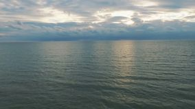 Vuelo sobre el mar apenas sobre las ondas que hacen frente a la puesta del sol Cantidad aérea del abejón metrajes