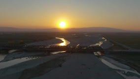 Vuelo sobre el puente con un río, una puesta del sol hermosa con las colinas almacen de video