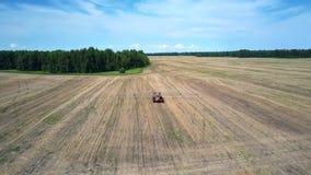 Vuelo sobre el tractor que conduce en campo cosechado grande almacen de metraje de vídeo
