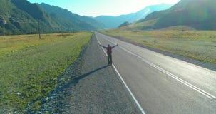 Vuelo sobre el turista del autostopista que camina en la carretera de asfalto Valle rural enorme en el d?a de verano Mochila que  metrajes