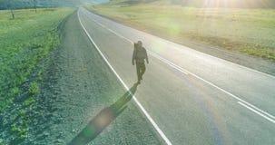 Vuelo sobre el turista del autostopista que camina en la carretera de asfalto Valle rural enorme en el d?a de verano Mochila que  almacen de video