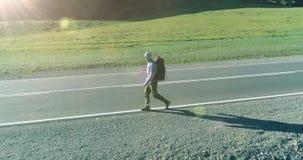 Vuelo sobre el turista del autostopista que camina en la carretera de asfalto Valle rural enorme en el d?a de verano Mochila que  almacen de metraje de vídeo