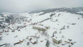 Vuelo sobre la ciudad en las montañas Ciudad nevada del invierno en los Cárpatos ucranianos almacen de video