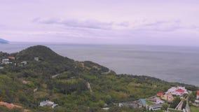 Vuelo sobre la costa montañosa con la pequeña ciudad debajo del cielo gris