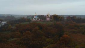 Vuelo sobre la niebla ucraniana de la mañana del pueblo y del convento almacen de video