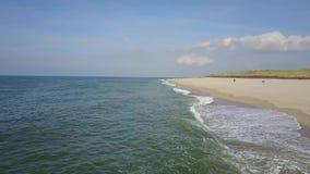 Vuelo sobre la playa casi vacía donde el mar besa la orilla almacen de metraje de vídeo