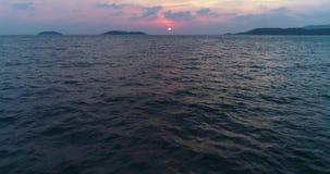 Vuelo sobre la superficie del agua hacia el sol en la puesta del sol metrajes