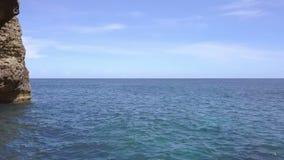 Vuelo sobre la superficie del mar a través de un arco de piedra Silueta del hombre de negocios Cowering almacen de video