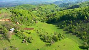Vuelo sobre las colinas y las casas verdes del pueblo, tierras de labrantío del campo Opini?n a?rea del abej?n 4k almacen de video