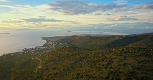 Vuelo sobre las montañas de la isla de Aegina a la ciudad de Egina, Grecia en la puesta del sol hermosa con el cielo dramático almacen de metraje de vídeo