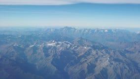 Vuelo sobre las montañas durante temporada de otoño Paisaje en los glaciares Visión aérea desde la ventana del aeroplano metrajes