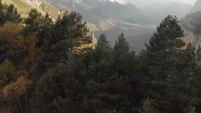 Vuelo sobre las montañas en el terreno montañoso sobre el bosque conífero con vistas al pueblo de montaña adentro almacen de metraje de vídeo