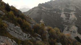 Vuelo sobre las montañas en el terreno montañoso sobre el bosque conífero con vistas al pueblo de montaña adentro metrajes