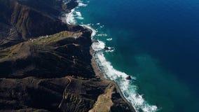 Vuelo sobre las montañas hermosas cerca de la orilla del océano almacen de metraje de vídeo