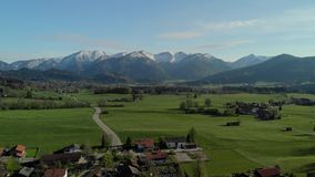 Vuelo sobre pueblo bávaro cerca de las montañas almacen de video