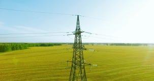 Vuelo vertical del movimiento cerca de la torre de alto voltaje de la electricidad y l?neas el?ctricas en el campo verde y amaril almacen de video