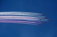 Vuelos de la demostración con los aviones en forma del jet coloreado fotografía de archivo