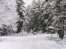 Vuelta del camino y coche el irse en bosque del invierno Imágenes de archivo libres de regalías
