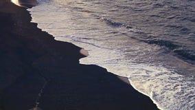 Vues fantastiques du littoral avec les vagues noires de sable et de ressac de la mer banque de vidéos
