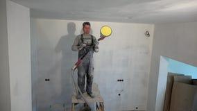 Vuil het poetsmiddelplafond van de stukadoormens met het schuren van molenmachine stock videobeelden