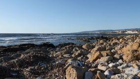 Vuil rotsachtig die strand met plastic flessen en document afval wordt gevuld Stapel van afval op het strand Langzame Motie stock video