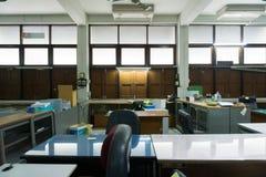 Vuil, slordig en verlaten bureau, slecht licht Royalty-vrije Stock Foto's