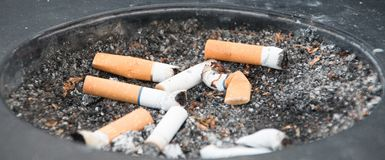 Vuil zwart asbakje met gerookte sigaretten Stock Fotografie
