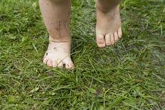Vuile benen van kind in de zomer op gras zonder schoenenclose-up Royalty-vrije Stock Afbeeldingen