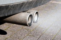 Vuile dubbele uitlaatpijpen van een auto, emissiestest Stock Afbeelding