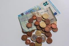 Vuile geld euro bankbiljetten en muntstukken op witte lijst Donker bedrijfsconcept stock foto
