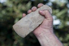 Vuile handholding handaxe Stock Foto