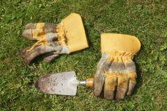 Vuile het tuinieren handschoenen en troffel Royalty-vrije Stock Foto's