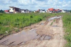 Vuile hobbelige weg die tot het nieuwe plattelandshuisjegebied leidt Royalty-vrije Stock Afbeelding