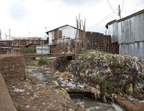 Vuile krottenwijk met vuilnis en slecht water stock afbeelding